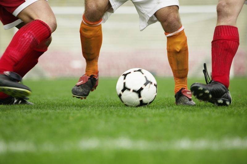 Soccer Player Dribbling Between Defenders